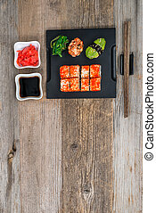 set of sushi and rolls with chopsticks on wooden table - set...