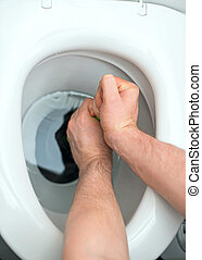 Plumber repairing toilet with hand plunger.