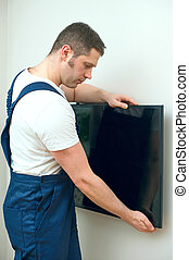 Man mounting TV on the wall.