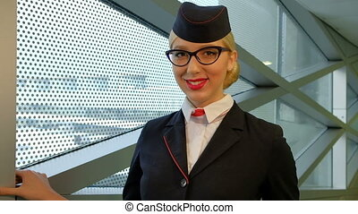 In airport stewardess with blond hair and glasses smiling affably.