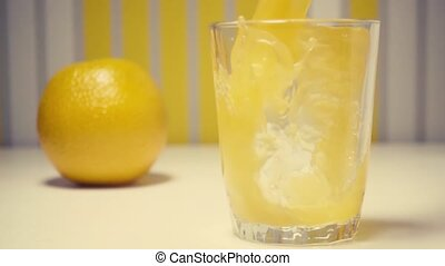 Slow motion orange juice with pulp is poured into a glass on...
