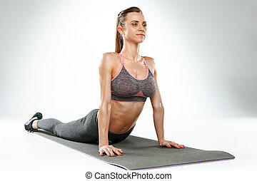 Beautiful slim brunette doing some stretching exercises in a...