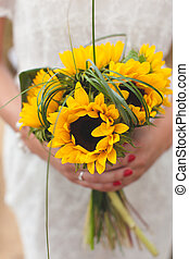 Girl in white dress holding a bouquet of sunflowers