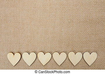 Wood hearts on hessian texture background, valentine...