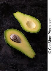 Top view on single avocado severed in half on dark tray -...