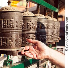 Prayer wheels and a hand - View of Prayer wheels and a hand