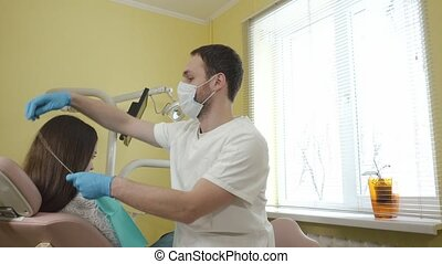 Male dentist prepares to examine a female patient in the...