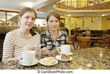 Beautiful girls relaxing at coffee-room with a cup of tea