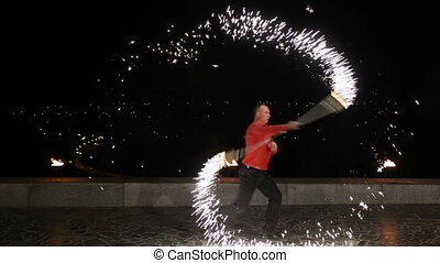 Fire show in the night. - Man and women twist fiery circles...