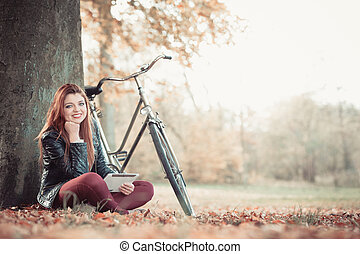 Girl under tree with bike. - Outdoor nature fitness internet...