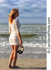 Beautiful young light brown hair woman walking on the beach...