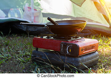 Portable gas stove and a frying pan in the camp.