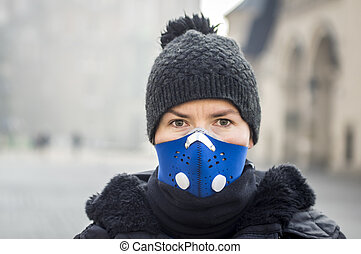 Woman using a mask, protecting herself from smog, Krakow,...