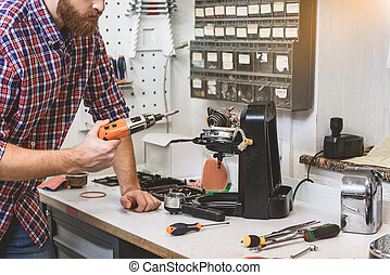 Bearded serious man holding drill - Male person is inclining...