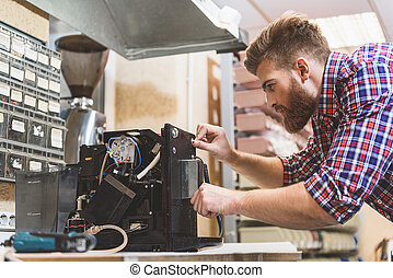 Serious man repairing broken coffee machine - Concentrated...