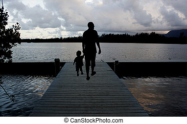 father and son walking on a pier