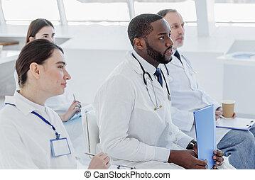 Pensive medical team diagnosing illness together - Attentive...
