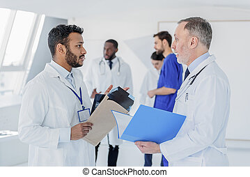 Young physician asking advice in senior general practitioner...