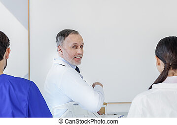 Professional physicians listening to interesting report -...