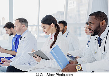 Skillful doctors listening to medical report - Concentrated...