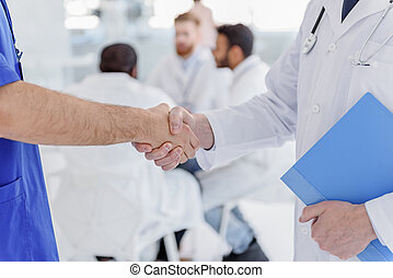Medical workers greeting each other by handshake - Close up...