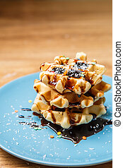 Homemade waffles sprinkles chocolate and coconut on blue...