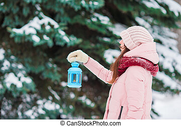 Young woman holding Christmas candlelight outdoors on beautiful winter snow day