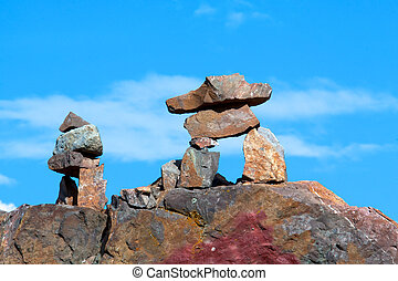 Two inukshuk sitting on a peak against a blue sky