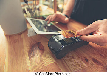 Barista taking credit card to do payment for visitor - Man...