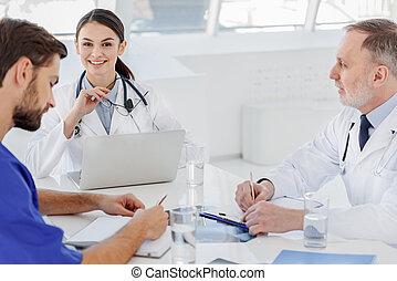 Professional medical team working together at hospital -...