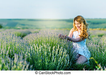 A girl in white dress picking flowers in the lavender field