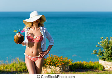 Young Woman drinking Coconut Cocktail at the beach. Summer...