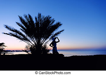 Girl silhouette at sunset. Beautiful sea view at sunset....