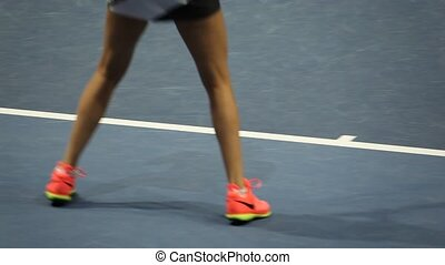 close-up of female legs in motion on the tennis court.