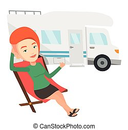 Woman sitting in chair in front of camper van. - Caucasian...