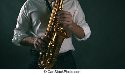 Locked down shot of musician playing saxophone in studio. Real time.