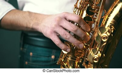 Close up shot of musician playing saxophone in studio. Locked down.