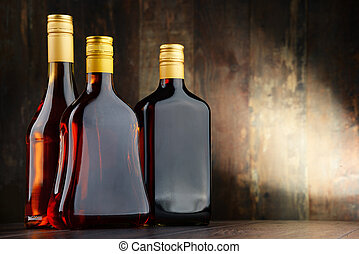 Bottles of assorted alcoholic beverages - Composition with...
