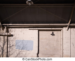 Metal door of an old warehouse with a canopy - Ramp of an...