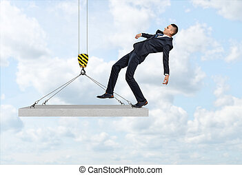 Businessman falling from the concrete slab suspended on the...