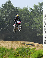 motocross racing - teenage boy jumping hills on a dirt bike