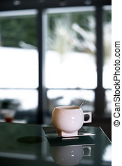 Elegant porcelain cup with stainless steel spoon and saucer