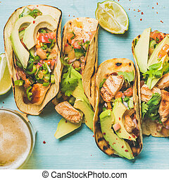 Healthy corn tortillas and beer over blue background, square...