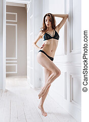 Cute model posing with right hand on the belt