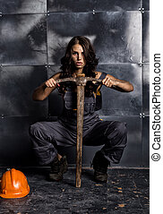 sexy female miner worker with pickaxe, in coveralls over his...