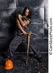 sexy female miner worker with pickaxe, in coveralls