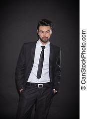 one young man posing suit, black background background