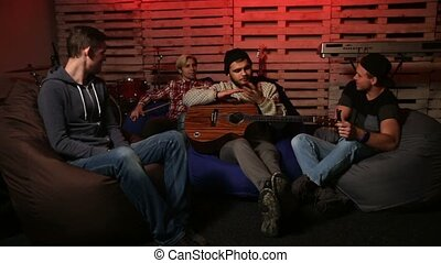 Music band relaxing after rehearsal in club - Four teenage...