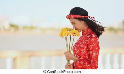 Beautiful Vietnamese girl in red traditional dress Ao Dai with yellow flowers.