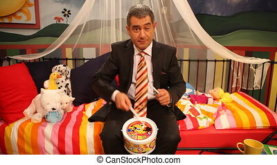 Mature man playing toy drum - Mature man wearing full suit...